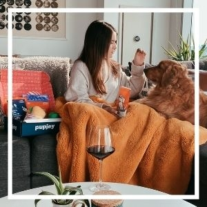 Woman sitting on couch with Golden Retriever opening a PupJoy box