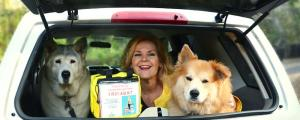Denise Fleck with two dogs and a pet first aid kit in car trunk